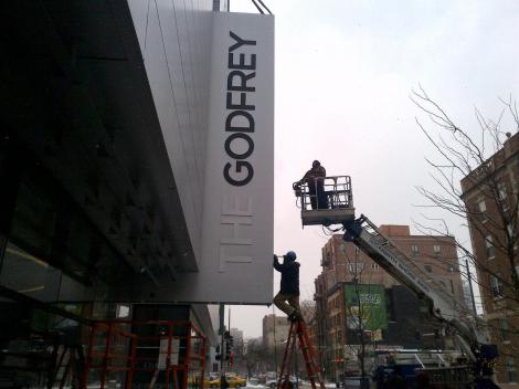 The final touches being applied during the installation of the hotel sign.